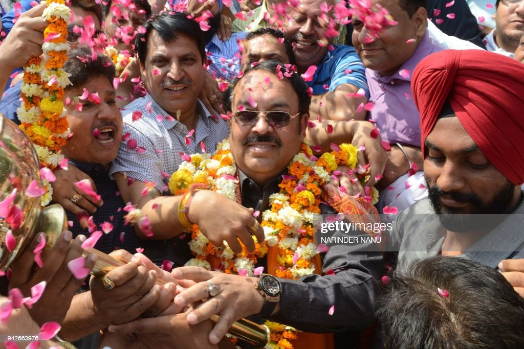 Newly appointed Punjab state Bharatiya Janata Party President Shwait Malik gestures next to BJP supporters during a visit in a temple in Amritsar on..