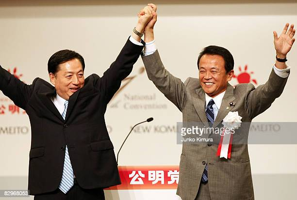 Newly appointed ruling Liberal Democratic Party president Taro Aso and the Chief Representative of New Komeito Akihiro Ota raise their arms in...