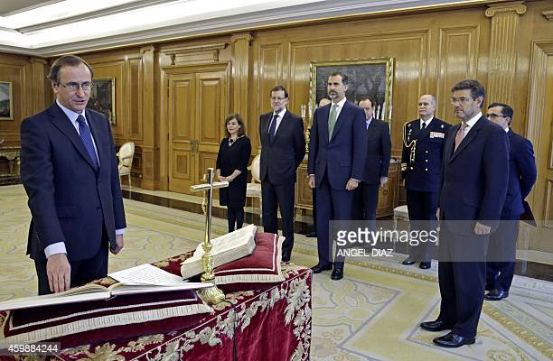 Newly appointed Spanish Health Minister Alfonso Alonso takes an oath as minister next to Spain's King Felipe VI Spanish Prime Minister Mariano Rajoy...
