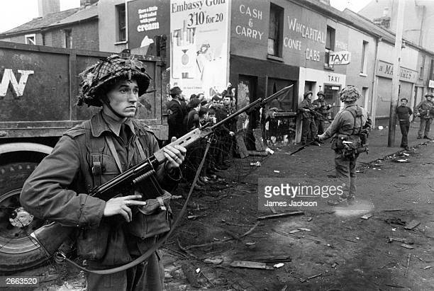 Newly arrived British soldiers stand on guard in the Catholic Fall's Road area of Belfast.