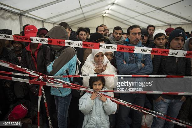 Newly arrived immigrants are kept behind a cordon as the wait to be let into a preregister site to allow them to be bussed to a newly opened asylum...