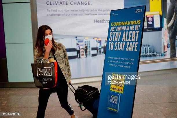 Newly arrived passenger wearing a face mask as a precaution against the novel coronavirus walks past a sign at Heathrow airport, west London, on May...