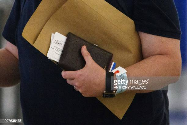 A newly arrived passenger wears a quarantine tracking wrist band to monitor new arrivals as a measure to stop the spread of the COVID19 coronavirus...