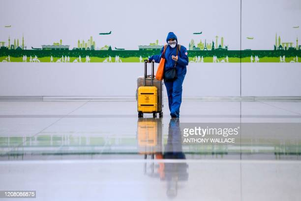 Newly arrived passenger wears protective gear and a face mask as a precautionary measure against the COVID-19 coronavirus, at the arrivals hall of...