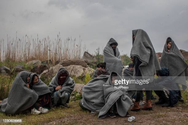 Newly arrived refugees from Afghanistan take shelter trying to get warm covered with blankets after they have spent the rainy night on a beach near...