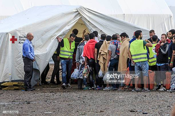 Newly arrived refugees wait in line inside a temporary tent camp on July 27 2015 in Dresden GermanyThe German Red Cross set up the camp last week and...