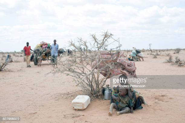 Newly arrived refugees wait with their belongings outside the IFOR refugee camp on July 30 2011 outside Dadaab Kenya Hundreds of thousands of people...