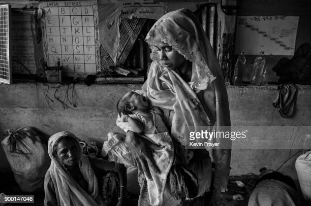 COX'S BAZAR BANGLADESH OCTOBER 27A newly arrived Rohingya Muslim refugee holds her baby inside a local school being used as a temporary shelter for...