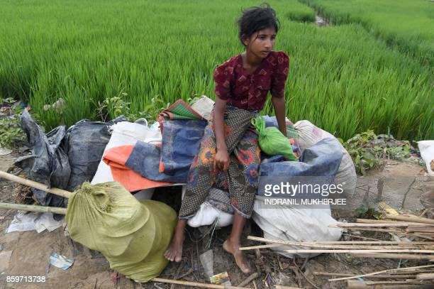 A newly arrived Rohingya refugee rests by the side of the road guarding her family's belongings on their way to Thangkhali refugee camp from...