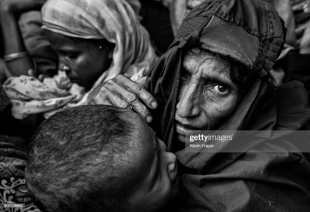 "COX'S BAZAR, BANGLADESH - OCTOBER 30: A newly arrived Rohingya refugee woman holds a child as they wait for food aid on October 30, 2017 near Cox's Bazar, Bangladesh. More than 600,000 Rohingya refugees have flooded into Bangladesh to flee an offensive by Myanmar's military that the United Nations has called ""a textbook example of ethnic cleansing"". The refugee population continues to swell further, with thousands more Rohingya Muslims making the perilous journey on foot toward the border, or paying smugglers to take them across by water in wooden boats. Hundreds are known to have died trying to escape, and survivors arrive with horrifying accounts of villages burned, women raped, and scores killed in the ""clearance operations"" by Myanmar's army and Buddhist mobs that were sparked by militant attacks on security posts in Rakhine state on August 25, 2017. What the Rohingya refugees flee to is a different kind of suffering in sprawling makeshift camps rife with fears of malnutrition, cholera, and other diseases. Aid organizations are struggling to keep pace with the scale of need and the staggering number of them — an estimated 60 percent — who are children arriving alone. Bangladesh, whose acceptance of the refugees has been praised by humanitarian officials for saving lives, has urged the creation of an internationally-recognized ""safe zone"" where refugees can return, though Rohingya Muslims have long been persecuted in predominantly Buddhist Myanmar. World leaders are still debating how to confront the country and its de facto leader, Aung San Suu Kyi, a Nobel Peace Prize laureate who championed democracy, but now appears unable or unwilling to stop the army's brutal crackdown. During a recent visit to Myanmar, U.S Secretary of State Rex Tillerson called for a ""credible"" probe into human rights violations against the Rohingya but said he would advise against full sanctions on the country."