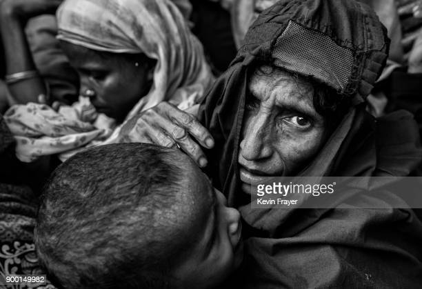 COX'S BAZAR BANGLADESH OCTOBER 30 A newly arrived Rohingya refugee woman holds a child as they wait for food aid on October 30 2017 near Cox's Bazar...