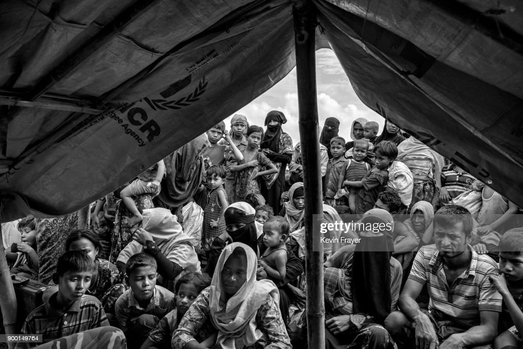 "COX'S BAZAR, BANGLADESH - OCTOBER 29: Newly arrived Rohingya refugees wait to be registered by IOM after arriving at Shah Porir Dwip on October 29, 2017 near Cox's Bazar, Bangladesh. More than 600,000 Rohingya refugees have flooded into Bangladesh to flee an offensive by Myanmar's military that the United Nations has called ""a textbook example of ethnic cleansing"". The refugee population continues to swell further, with thousands more Rohingya Muslims making the perilous journey on foot toward the border, or paying smugglers to take them across by water in wooden boats. Hundreds are known to have died trying to escape, and survivors arrive with horrifying accounts of villages burned, women raped, and scores killed in the ""clearance operations"" by Myanmar's army and Buddhist mobs that were sparked by militant attacks on security posts in Rakhine state on August 25, 2017. What the Rohingya refugees flee to is a different kind of suffering in sprawling makeshift camps rife with fears of malnutrition, cholera, and other diseases. Aid organizations are struggling to keep pace with the scale of need and the staggering number of them — an estimated 60 percent — who are children arriving alone. Bangladesh, whose acceptance of the refugees has been praised by humanitarian officials for saving lives, has urged the creation of an internationally-recognized ""safe zone"" where refugees can return, though Rohingya Muslims have long been persecuted in predominantly Buddhist Myanmar. World leaders are still debating how to confront the country and its de facto leader, Aung San Suu Kyi, a Nobel Peace Prize laureate who championed democracy, but now appears unable or unwilling to stop the army's brutal crackdown. During a recent visit to Myanmar, U.S Secretary of State Rex Tillerson called for a ""credible"" probe into human rights violations against the Rohingya but said he would advise against full sanctions on the country."