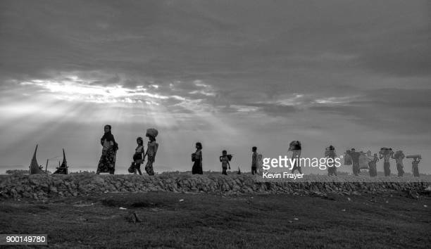 COX'S BAZAR BANGLADESH OCTOBER 29 Newly arrived Rohingya refugees walk along an old road after arriving at Shah Porir Dwip on October 29 2017 near...