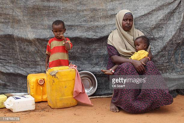 Newly arrived Somali refugees sit outside their hut on the edge of the Hagadera refugee camp which makes up part of the giant Dadaab refugee...