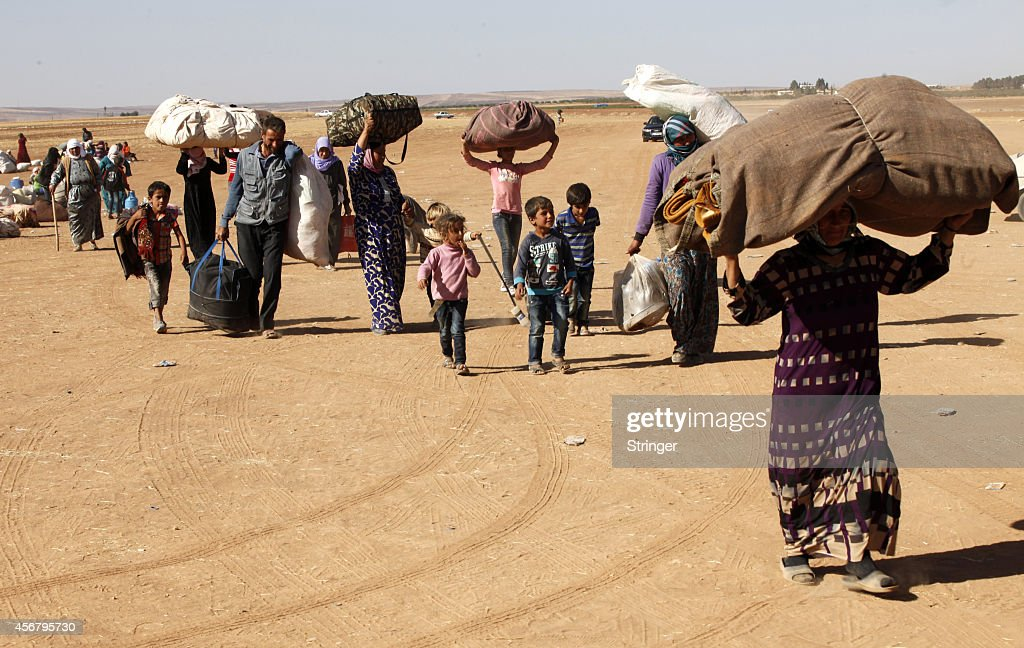 Newly arrived Syrian Kurdish refugees walk with their belongings after crossing into Turkey from the Syrian border town of Kobani on September 26, 2014 near the southeastern town of Suruc in Sanliurfa province, Turkey. .