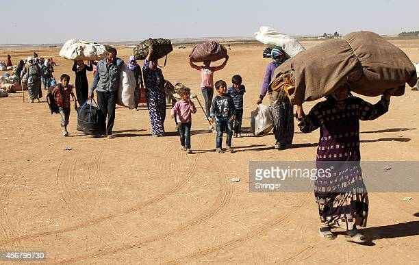 Newly arrived Syrian Kurdish refugees walk with their belongings after crossing into Turkey from the Syrian border town of Kobani on September 26...