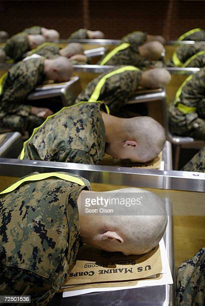 Newly arriving Marine recruits sit with their faces on desks as they wait for the next phase of processing during the early morning hours at the...
