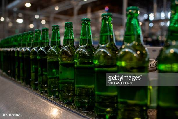 Newly bottle beers are seen on their way to the labelling machine in the InBev beer factory in Ogun State outside Lagos on November 7 2018 Gigantic...