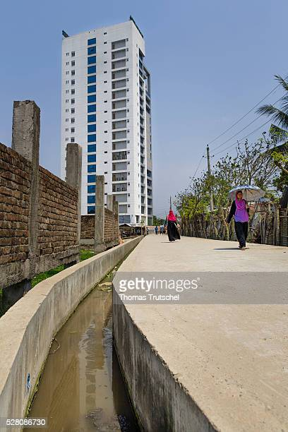 A newly built building is captured behind a newly built street with a sewer on April 11 2016 in Khulna Bangladesh