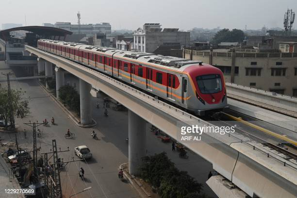 Newly built Orange Line Metro Train , a metro project planned under the China-Pakistan Economic Corridor , drives through on a track after its...