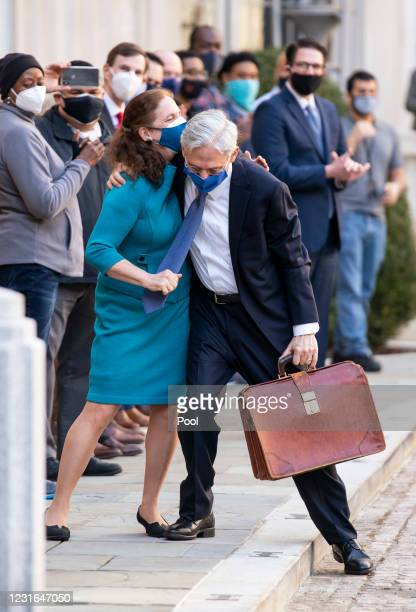 Newly confirmed U.S. Attorney General Merrick Garland hugs his wife Lynn as he arrives for his first day at the Department of Justice March 11, 2021...