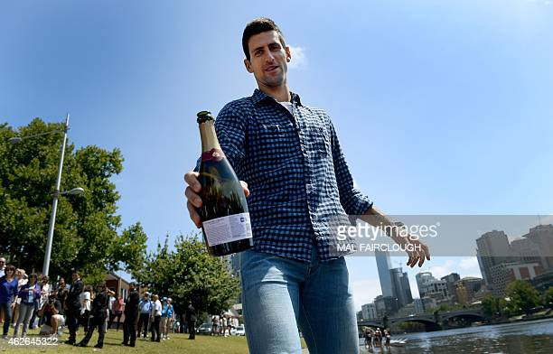 Newly crowned Australian Open champion Novak Djokovic of Serbia hands over a bottle of champagne to the photographer during a photo session with the...