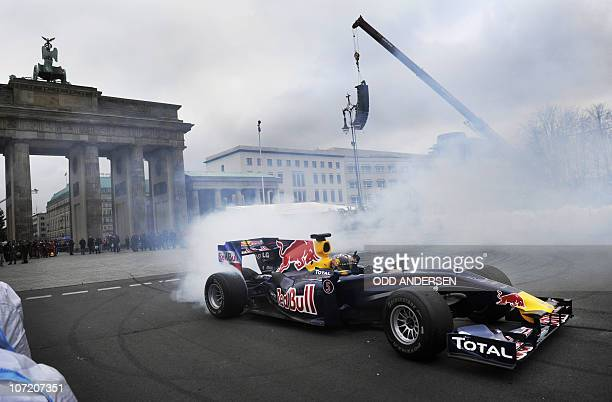 Newly crowned Formula One World Champion Sebastian Vettel burns rubber in front of the landmark Brandenburger Gate during a lap of honour on the 17th...