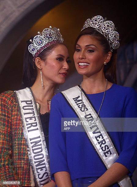 Newly crowned Miss Indonesia 2014 Elvira Devinamira and Miss Universe Maria Gabriela Isler from Venezuela appear together on stage during a visit to...
