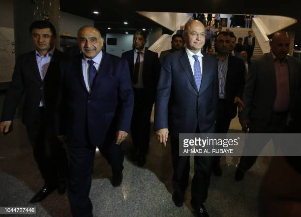 Newly designated Iraqi Prime Minister Adel Abdul Mahdi walks out of the Parliament with newlyelected Iraqi President Barham Saleh in Baghdad on...
