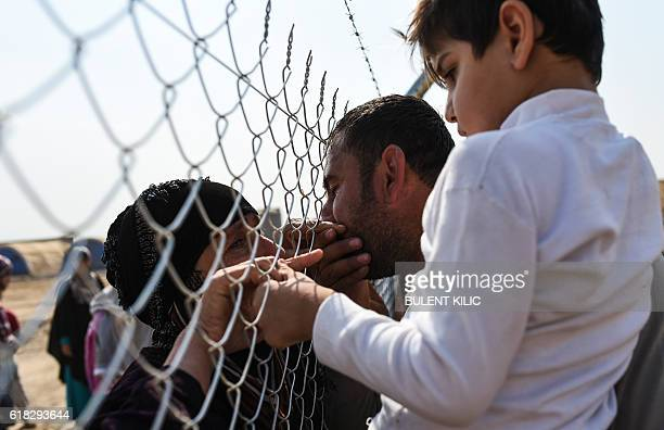 A newly displaced Iraqi woman who fled from the city of Mosul Iraq's last major Islamic State group stronghold kisses cries as she is reunited with...