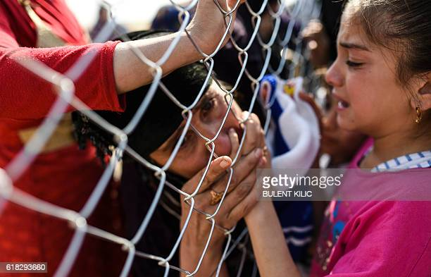 A newly displaced Iraqi woman who fled from the city of Mosul Iraq's last major Islamic State group stronghold kisses a child's hand as she is...