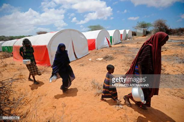 Newly displaced Somali women and children walk to a food distribution at the Kaxda district outskirts of Mogadishu on April 9 2017 Somalia a Horn of...