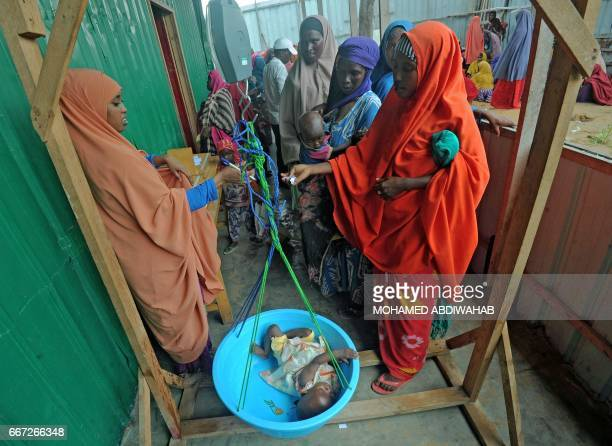 Newly displaced Somali women weigh their malnourished children as they try to receive medical treatment on the outskirts of Mogadishu on April 11...