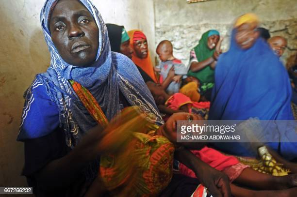 Newly displaced Somali women with their malnourished children receive medical treatment on the outskirts of Mogadishu on April 11 2017 The United...