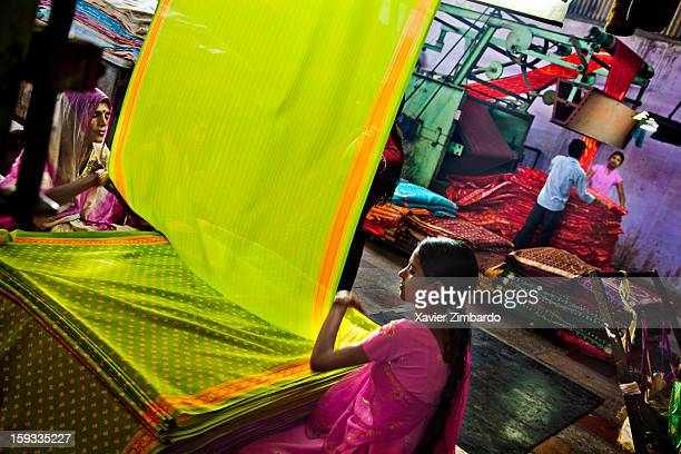 Newly dyed fabric being washed rolled printed and folded by workers at a textile dyeing factory in Rajasthan India on January 13 2012