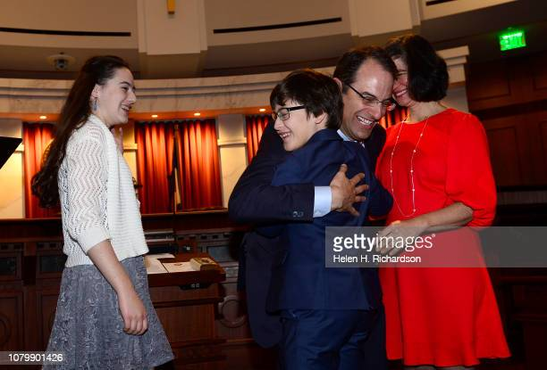 Newly elected Attorney General Phil Weiser gives a hug to his son Sammy after receiving the oath of office during his investiture ceremony in the...