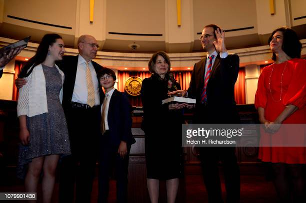 Newly elected Attorney General Phil Weiser raises his left hand as he takes the oath of office given to him by Judge David Ebel not shown during his...