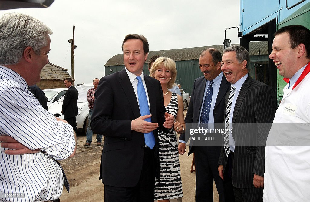 Newly elected British Prime Minister David Cameron (C) meets staff at Mash Direct farm in Co Down on May 20, 2010, during Mr Cameron's first engagement in the region since taking office. AFP PHOTO/Paul Faith
