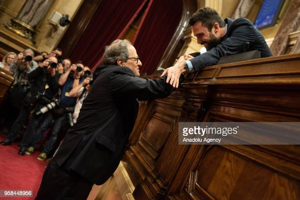 Newly elected Catalan regional president Quim Torra shakes hands to Catalan parliament speaker Roger Torrent during a session at the Catalan...