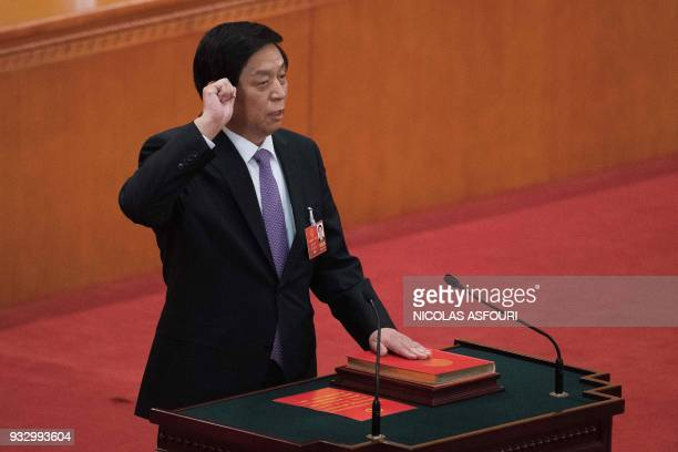 Newly elected Chairman of the National People's Congress Li Zhanshu swears an oath after being elected during the fifth plenary session of the first...