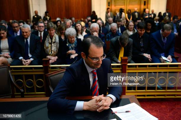 Newly elected Colorado State Attorney General Phil Weiser bows his head in prayer during a benediction given by Pastor Anitha Jones during his...