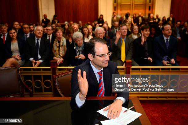 Newly elected Colorado State Attorney General Phil Weiser holds up his hand in prayer with others during a benediction given by Pastor Anitha Jones...