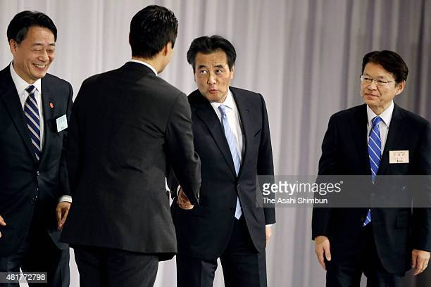 Newly elected Democratic Party President Katsuya Okada shakes hands with candidate Goshi Hosono while Akira Nagatsuma and outgoing president Banri...