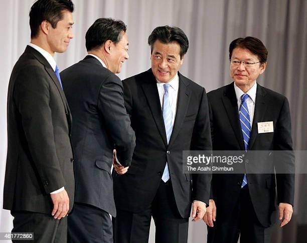 Newly elected Democratic Party President Katsuya Okada shakes hands with outgoing president Banri Kaieda while candidate Goshi Hosono and Akira...