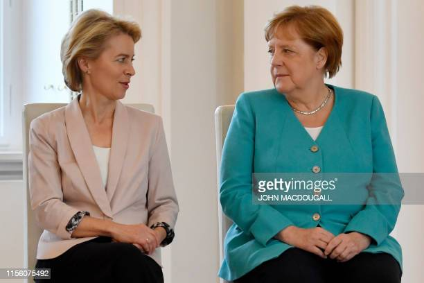 Newly elected European Commission President and outgoing German Defence Minister Ursula von der Leyen sits next to German Chancellor Angela Merkel...