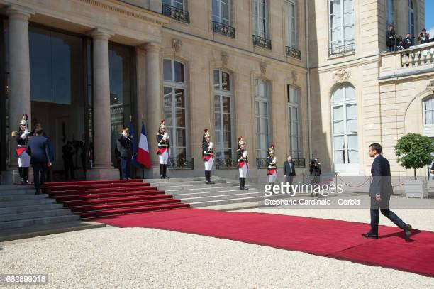 Newly elected French President Emmanuel Macron walks back along the red carpet after escorting outgoing French President Francois Hollande, after a...