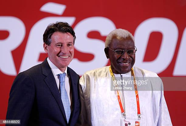 Newly elected IAAF president Lord Sebastian Coe stands with outgoing president Lamine Diack during the 50th IAAF Congress at the China National...