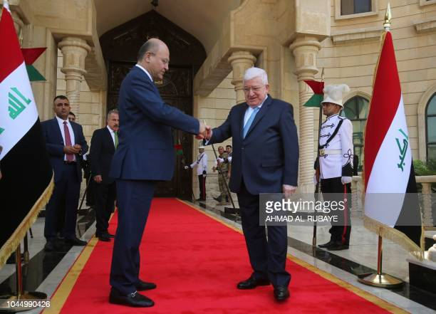 Newly elected Iraqi President Kurdish Barham Saleh greets his predecessor Fuad Masum during the handing over ceremony in Baghdad on October 3 2018...