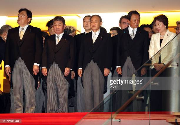 Newly elected Japanese Prime Minister Yoshihide Suga and his cabinet members line up as they prepare for a photo session after their first cabinet...