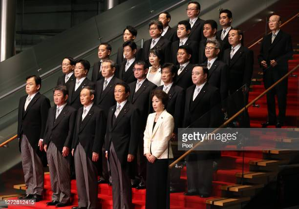 Newly elected Japanese Prime Minister Yoshihide Suga poses with his cabinet members for group photos after their first cabinet meeting at the prime...